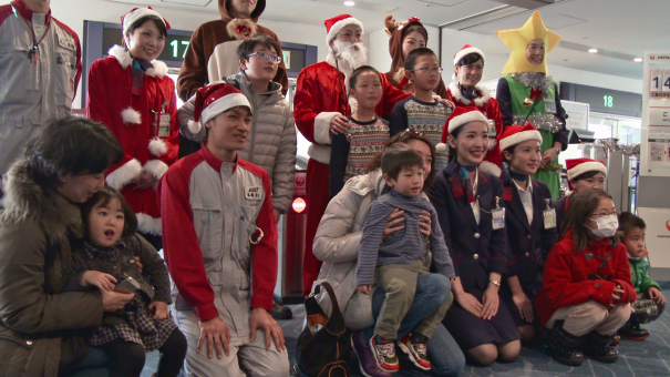 サンタクロースやトナカイ、JALスタッフらと記念写真を撮る乗客 [photo: Travel Online News]