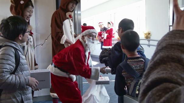 搭乗口で乗客にクリスマス・プレゼントを配布 [photo: Trave Online News]